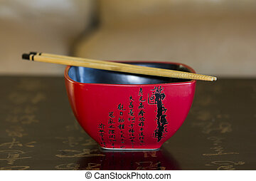 Red chinese rice bowl decorated with chinese calligraphy with chopsticks on its top lying on the surface of black chinese table likewise decorated with calligraphy