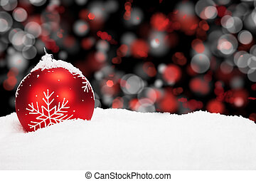 red christmas ball in snow with abstract background lights