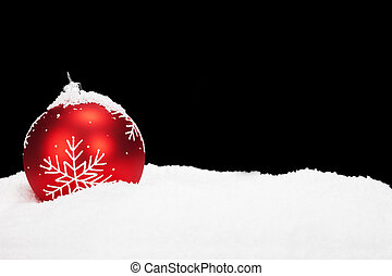 red christmas ball in snow with black background