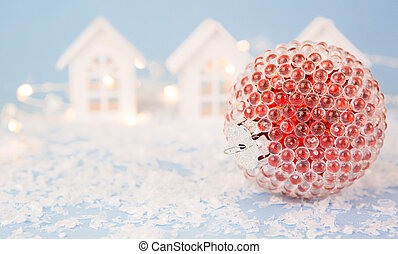 Red Christmas ball on a blue background with artificial snow and lights of garlands in bokeh. Festive background, new year. Copy space. Small white wooden houses, a street with houses in the blur