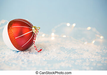 Red Christmas ball on a blue background with artificial snow and lights of garlands in bokeh. Festive background, new year. Copy space