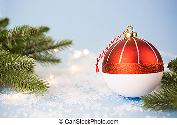 Red Christmas ball on a blue background with artificial snow, the branches of spruce and lights of garlands in bokeh. Festive background, new year. Copy space