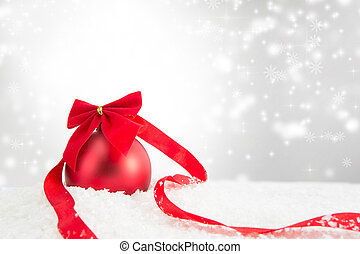 Red Christmas ball on a white snow surface over gray background