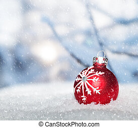 Red Christmas ball on snow against snowing winter landscape.