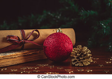Red christmas ball with a cone and scroll letter on the old book on the wooden table close up