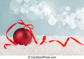 red Christmas ball with a scarlet satin bow in the snow on a blue background with bokeh lights. happy new year card