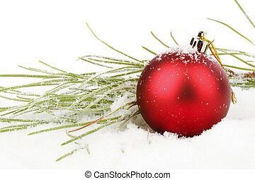 Red christmas ball with fir in the snow