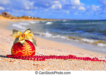 Red christmas ball with golden bow on sand
