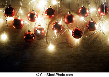 Red christmas balls hanging on threads and garland of christmas lights on light oak wood background. New year and christmas composition. Copy space