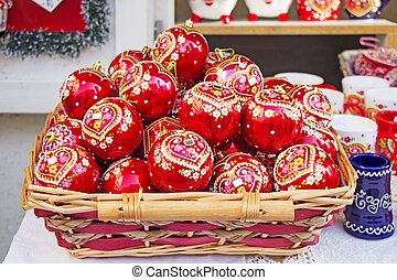 Red Christmas balls in wicker basket, hand painted with traditional Croatian decorations