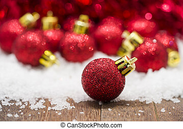 Red Christmas balls on snow against red bokeh background