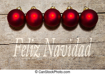 Red christmas balls on wooden table, spanish text, merry christmas
