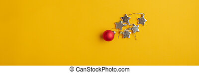 Red Christmas bauble and golden stars on yellow background