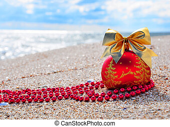 Red christmas bauble with golden bow on sand on beach