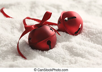 Red Christmas bells with ribbon in snow