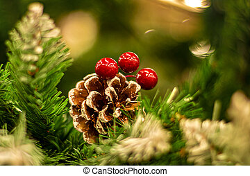 Red Christmas Berries on branches of New Year Xmas tree. Berries and bump on Christmas tree. Defocused christmas background. Concept of new year 2021.