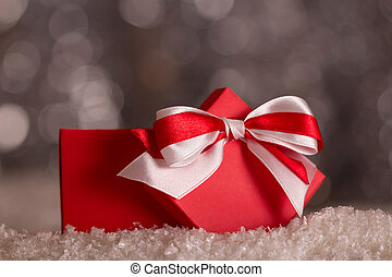 Red Christmas box with bow in the snow on gray background with bokeh effect