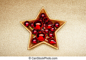 red christmas decoration in a golden star-shaped bowl on a golden background