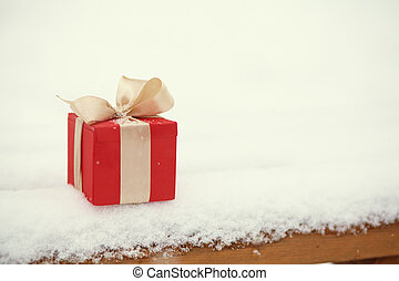 red Christmas gift box in the winter snow outdoors.