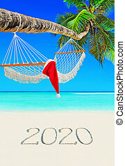 Red Christmas hat on wooden hammock under palm tree at tropical Seychelles beach with happy new year 2020 caption on sand.