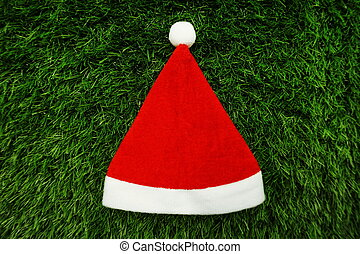 Red Christmas hat with space copy on green artificial grass background