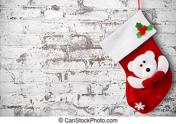Red christmas sock on white brick wall