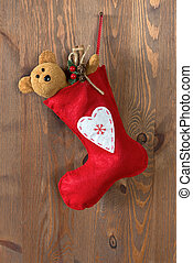Red Christmas stocking on an old door.