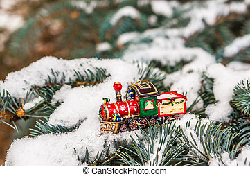 Red Christmas toy train on snowy branch fir