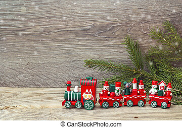 Red Christmas toy train with fir branches and copy space.