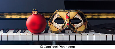 Red Chritmas ball and carnival mask on piano keyboard, front view
