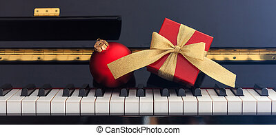 Red Chritmas ball and gift box on piano keyboard, front view