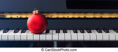 Red Chritmas ball on piano keyboard, front view