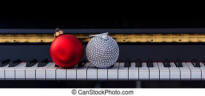 Red Chritmas balls on piano keyboard, front view