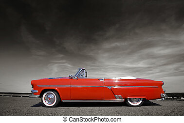 Shiny red classic car against cloudy sky in sepia