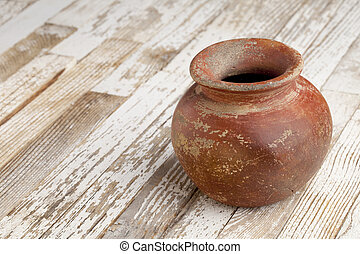 small red and brown clay plant pot (mass produced planter) with rough, grunge finish, on white wood background
