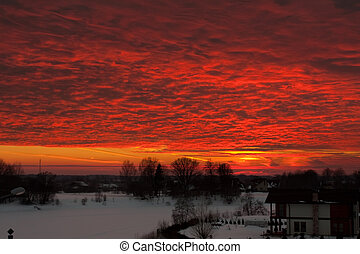 Red clouds lit by sun in winter time