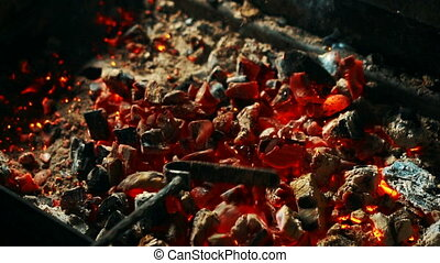 Red coals are being mixed by rake in grill station, close up.
