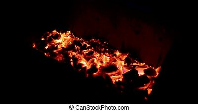 red coals smolder in a barbecue