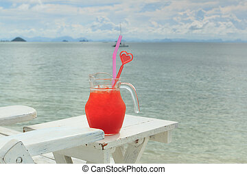 Red cocktail on white table set over ocean