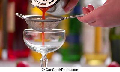 Red cocktail pours through sieve.