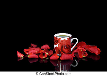 Red coffee cup among rose petals on the black background