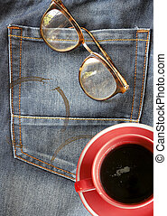 Red coffee cup on jeans background with eyeglasses (relax concept)