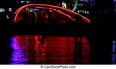 Red color disco - People walk under the disco laser show.
