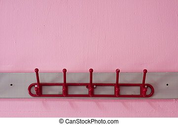 red coloured cloth hanger on a pink wall