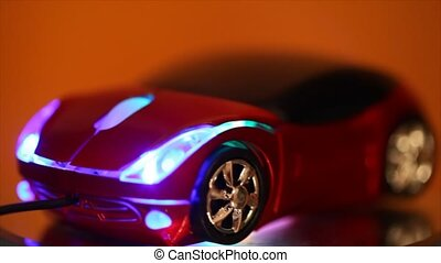 computer mouse in form of automobile glows blue backlight and rotates on rotating stand, side view