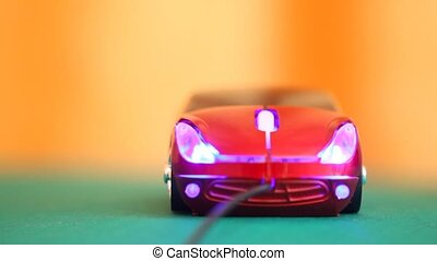 computer mouse in form of automobile glows blue backlight and rotates