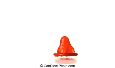 Red condom falling on white background in slow motion