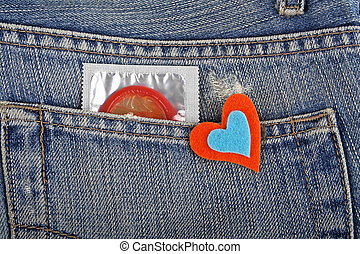 Red condom in blue jeans pocket and colored heart