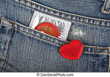 Red condom in blue jeans pocket and red heart
