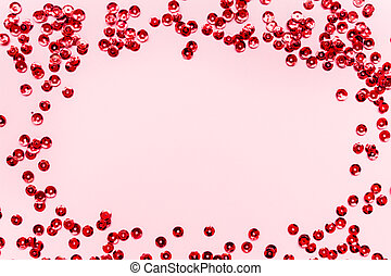 Red confetti on pink background. Top view, flat lay, mockup, overhead. Copy space for text. Bright and festive holiday background. For Christmas, New year, Mother's day, Valentines Day, Birthday, holiday background